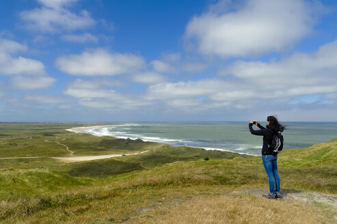 Denmark, Jutland, Bulbjerg, woman taking pictures in dune landscape - UMF00872