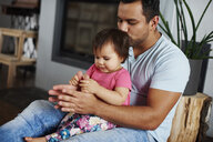 Affectionate father embracing and kissing his daughter at home - ABIF01082