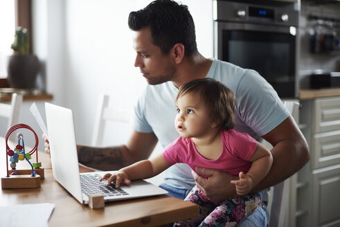 Father with baby girl using laptop on table at home - ABIF01085