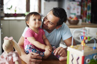 Smiling father with baby girl at home - ABIF01088