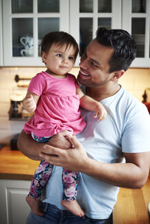 Smiling father holding baby girl in kitchen at home - ABIF01091