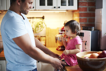 Smiling father looking at baby girl eating a tangerine on counter in kitchen at home - ABIF01094