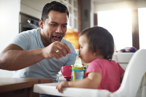 Father feeding baby girl sitting in high chair at home - ABIF01097