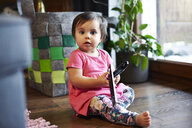 Portrait of cute baby girl sitting on the floor at home holding remote control - ABIF01100
