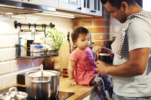 Father and baby girl cooking together in kitchen at home - ABIF01103