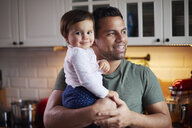 Smiling father holding baby girl in kitchen at home - ABIF01115