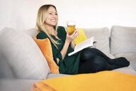 Portrait of relaxed woman sitting on the couch with book and drinking glass - DMOF00078