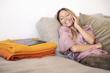 Portrait of laughing woman on the phone relaxing on couch at home - DMOF00084