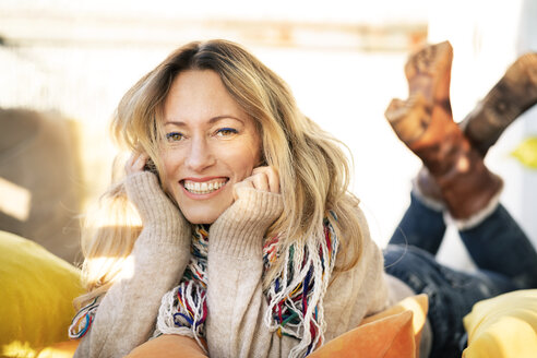 Portrait of smiling blond mature woman relaxing in winter garden - DMOF00093