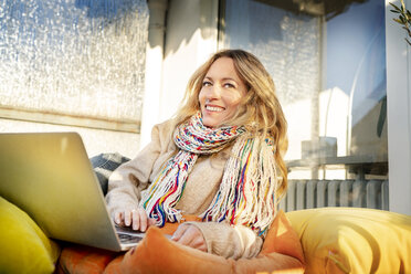 Portrait of smiling blond mature woman relaxing in winter garden using laptop - DMOF00096