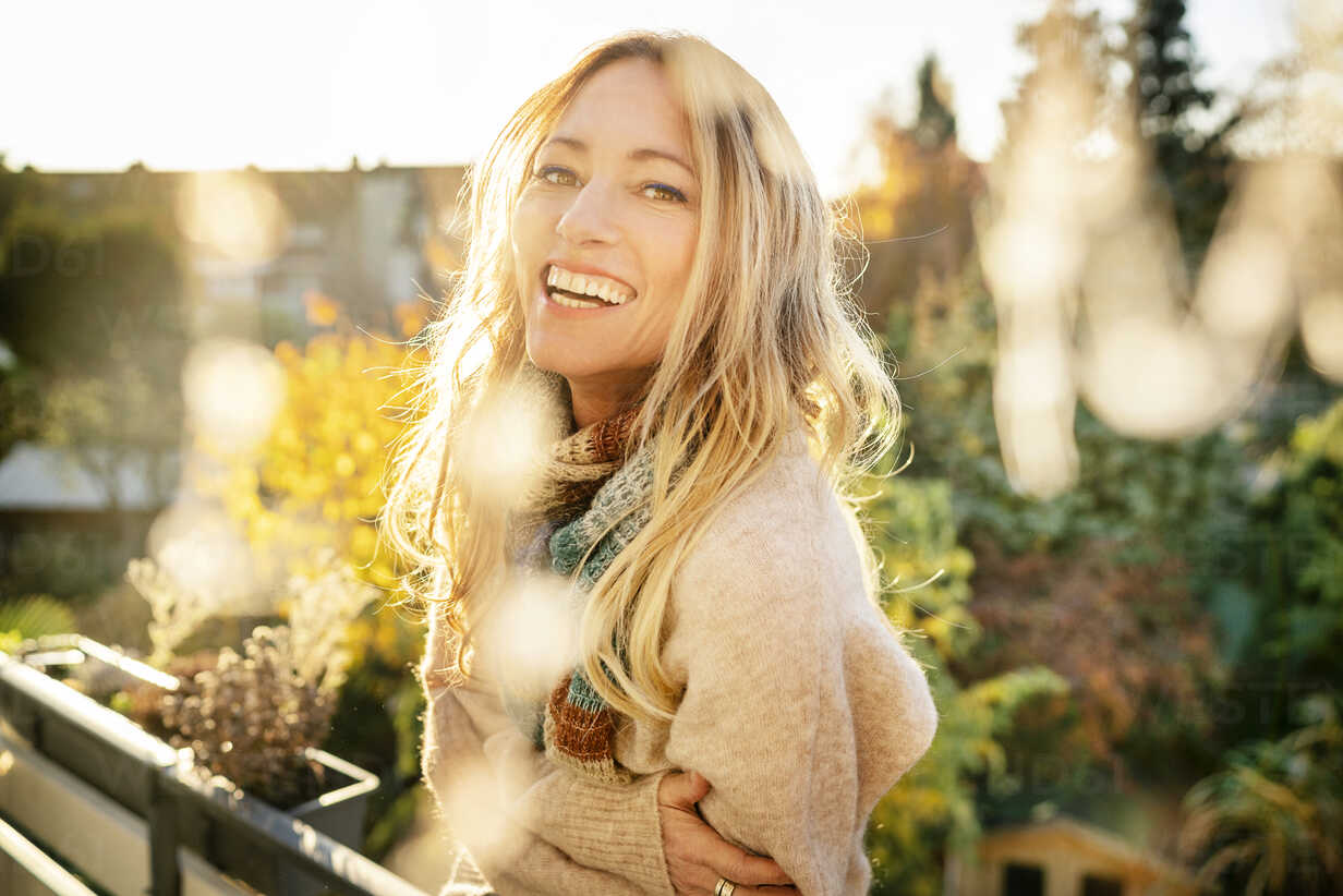 Portrait of laughing blond mature woman on balcony at autumn - DMOF00099 - Dirk Moll/Westend61