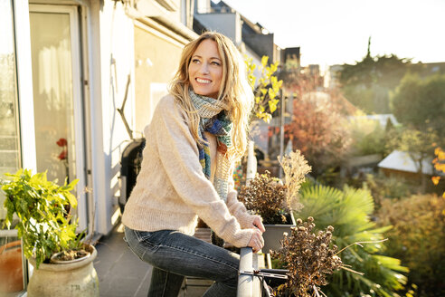 Portrait of smiling blond mature woman standing on balcony at autumn - DMOF00102