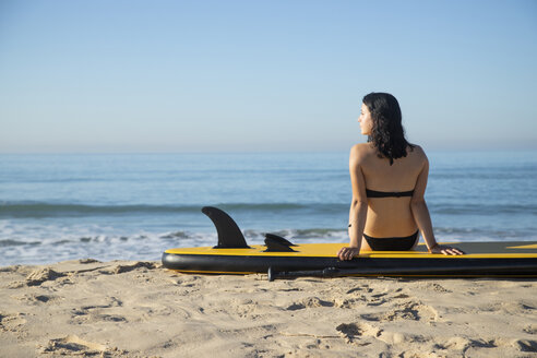 Spain, Andalusia, Tarifa, woman sitting on stand up paddle board on the beach - KBF00393