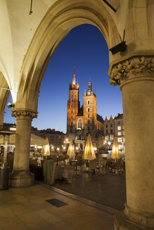 Poland, Krakow, city by night, view to St. Mary Church from the arcade of the Coth Hall (Sukiennice) in Old Town - ABOF00407