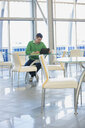 Businessman with digital tablet working in office cafeteria - HEROF04195