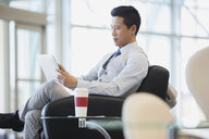 Businessman with digital tablet and coffee in lobby - HEROF04243