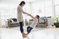 Daughter dancing on mothers feet in living room - HEROF04258