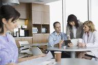 Doctors using digital tablet in break room - HEROF04267