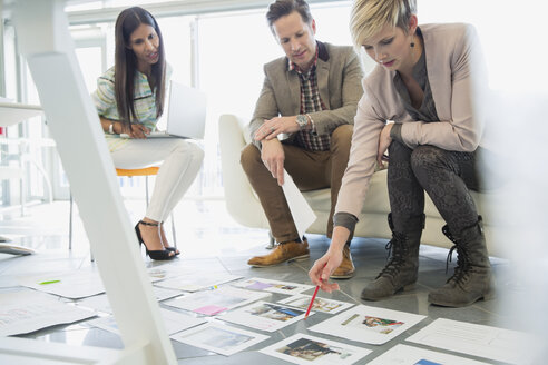 Creative business people looking at proofs in office - HEROF04351