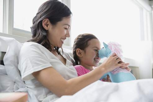 Mother and daughter with stuffed animal in bed - HEROF04426