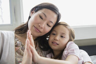 Mother and daughter touching hands - HEROF04444
