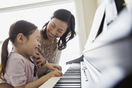 Mother teaching daughter to play piano - HEROF04447