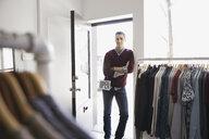 Portrait of business owner in clothing shop doorway - HEROF04477