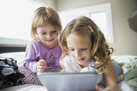 Girls using digital tablet on bed - HEROF04558