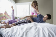 Fathers and daughters playing on bed - HEROF04567
