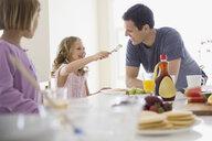 Family eating breakfast in kitchen - HEROF04579