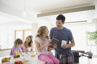 Family with digital tablet eating breakfast in kitchen - HEROF04585