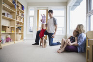 Father helping daughter do handstand in living room - HEROF04597