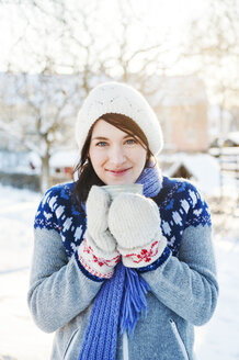 Young woman with cup in snow in Enskede, Sweden - FOLF09661