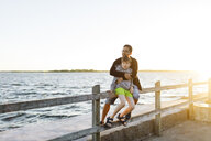 Father and son sitting on a pier at sunset in Blekinge, Sweden - FOLF09769