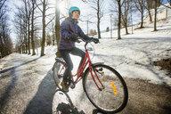 Mid adult woman riding a bicycle in Lahti, Finland - FOLF09853