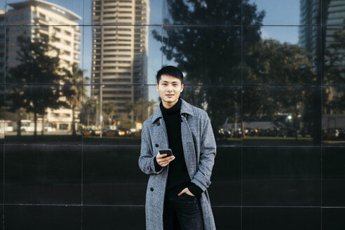 Spain, Barcelona, portrait of young man with cell phone wearing black turtleneck pullover and grey coat - JRFF02444