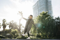 Spain, Barcelona, happy young man balancing on a wall at backlight - JRFF02450
