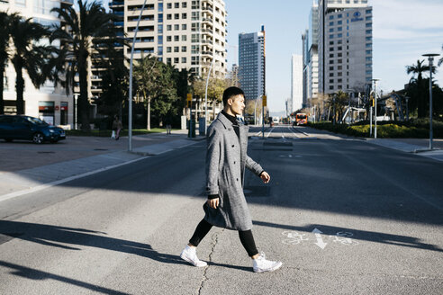 Spain, Barcelona, young man crossing the street - JRFF02459