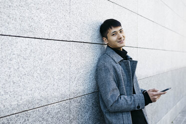 Portrait of smiling young man with cell phone leaning against wall - JRFF02465