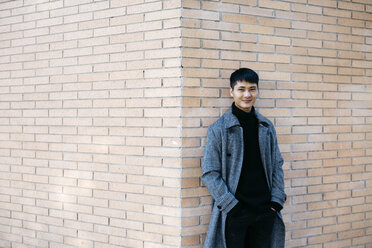Portrait of smiling young man wearing grey coat and black turtleneck pullover leaning against wall - JRFF02471
