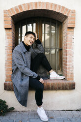 Laughing young man wearing fashionable coat sitting on window sill outdoors - JRFF02480