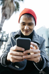 Spain, Barcelona, portrait of smiling young man looking at cell phone - JRFF02492