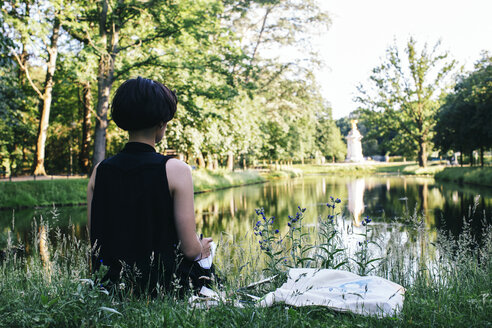 Back view of an artist sitting on a meadow near water in a park drawing - JUBF00314