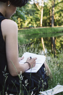 Artist sitting on a meadow near water drawing, partial view - JUBF00317
