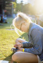Teenage girl sitting in a park in Copenhagen - FOLF09914