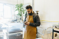 Small business owner in his coffee roaster shop - FOLF09983