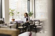 Barista using laptop at cafe table - FOLF10034