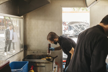 Chef cooking burgers on the grill in a food truck - FOLF10094