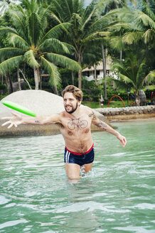 Young man throwing a frisbee in a swimming pool in Koh Samui, Thailand - FOLF10187