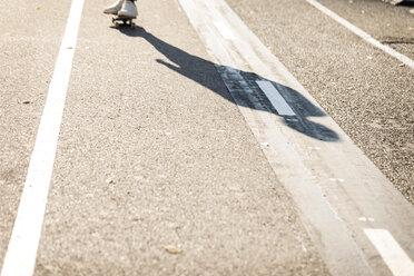 Shadow of man skateboarding on cycle path - VABF02080